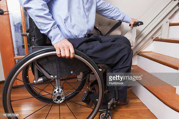 man with spinal cord injury getting into his motorized stair lift - elevador de escada imagens e fotografias de stock
