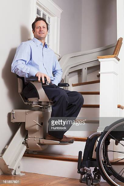 man with spinal cord injury going up in his motorized stair lift - elevador de escada imagens e fotografias de stock