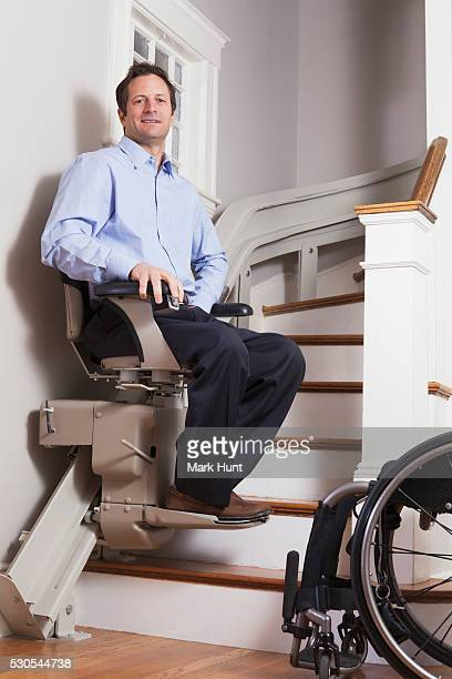 man with spinal cord injury going up in his motorized stair lift - quadriplegic stock photos and pictures