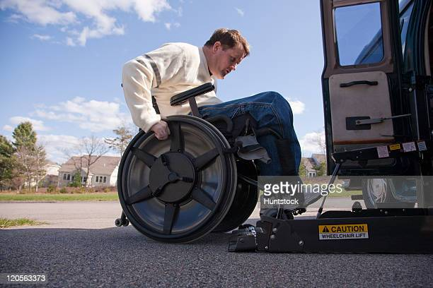 Man with spinal cord injury in a wheelchair getting on his motorized lift of a wheelchair accessible van