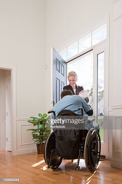 Man with spinal cord injury in a wheelchair greeting a woman at the door of his accessible home