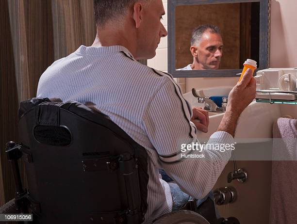 man with spinal cord injury in a wheelchair looking at a pill bottle - pessoas com deficiência imagens e fotografias de stock