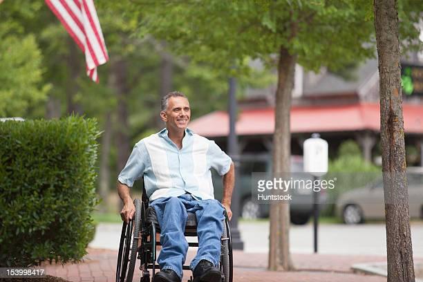hombre con la médula espinal lesión en una silla de ruedas en ladrillo - quadriplegic fotografías e imágenes de stock