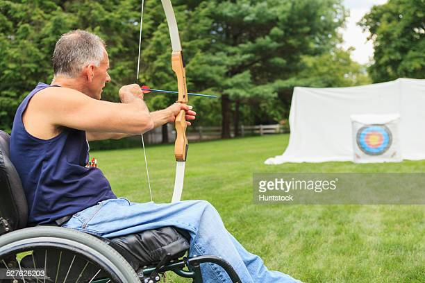 man with spinal cord injury in wheelchair aiming his bow and arrow for archery practice - ターゲット射撃 ストックフォトと画像
