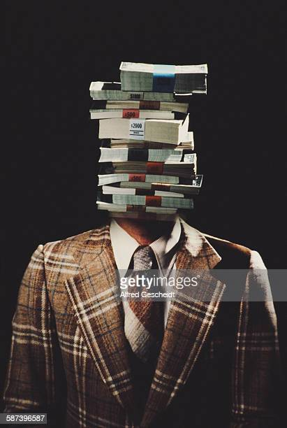 A man with stacks of US banknotes for a head circa 1985