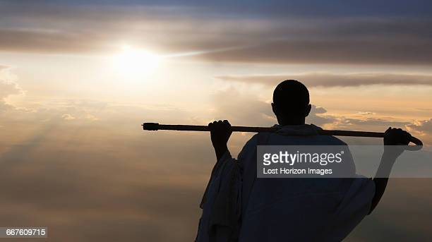 man with stick watching sunset, lalibela, ethiopia - lalibela stock photos and pictures