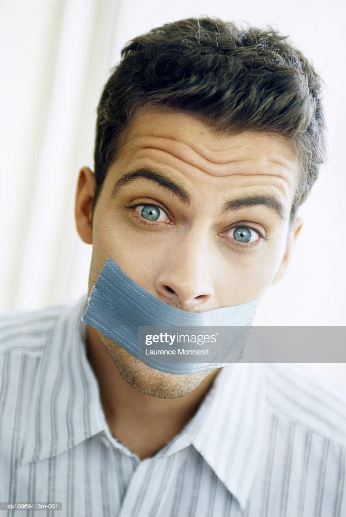 Man with sticky tape on mouth, portrait, close-up : Stock Photo