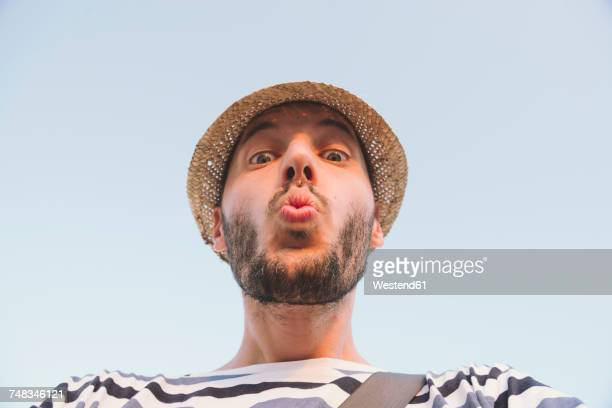 man with straw hat kissing to the camera - low angle view stock pictures, royalty-free photos & images