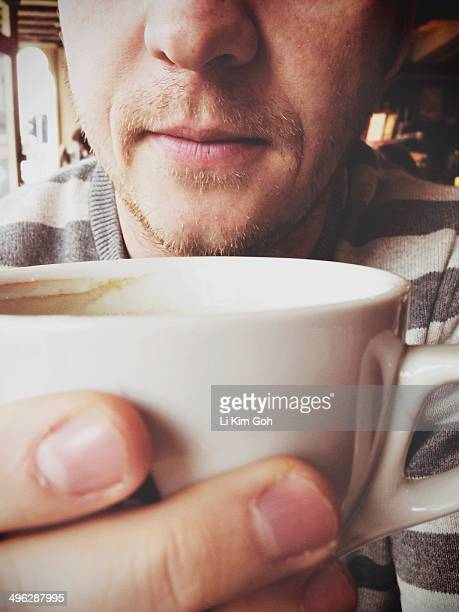 Man with stubble drinking coffee