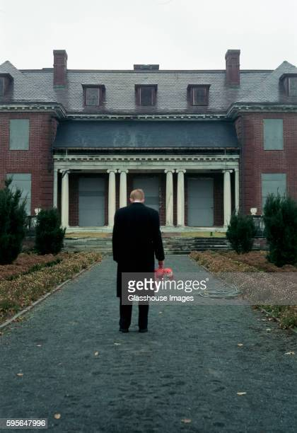 man with stuffed animal standing by old mansion - wellesley massachusetts stock pictures, royalty-free photos & images