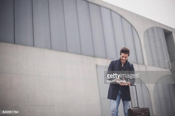 スーツケースと携帯を持つ男 - スマートカジュアル ストックフォトと画像