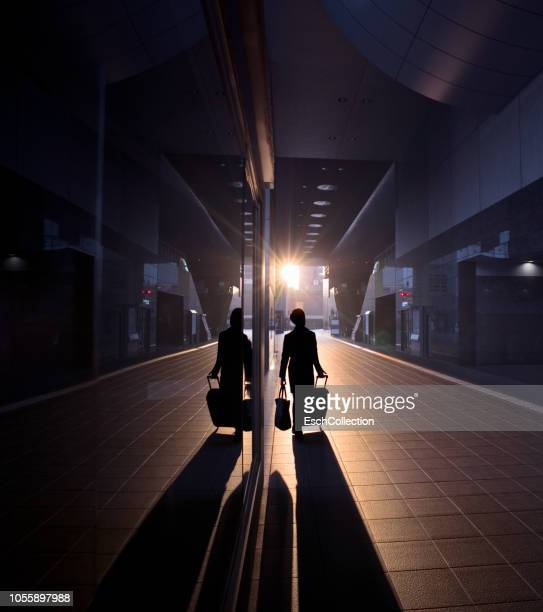 man with suitcase arriving at train station at dawn - high contrast stock pictures, royalty-free photos & images