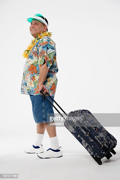 Man with suitcase in Hawaiian shirt against white background, smiling