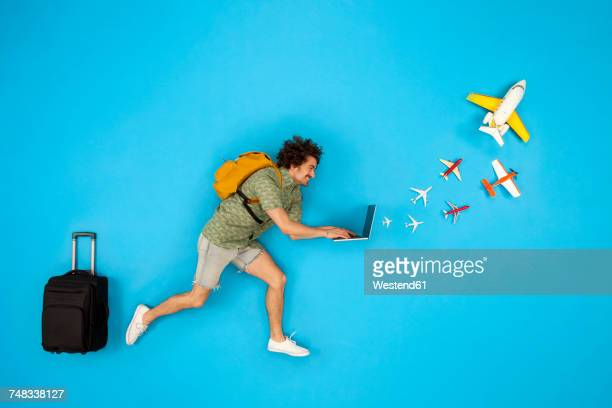 Man with suitcase looking at laptop with airplanes coming out