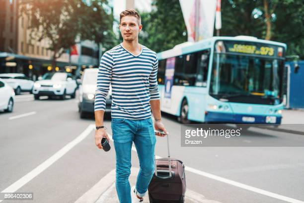 man with suitcase waiting for public transport - northern european descent stock pictures, royalty-free photos & images