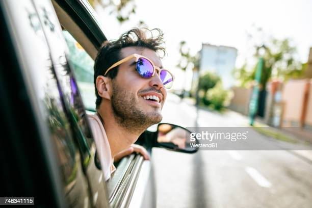 Man with sunglasses leaning out the window of a car in motion