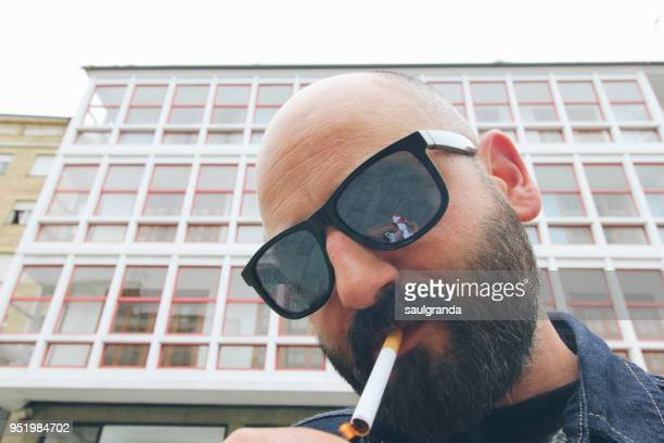 Man with sunglasses lightning a cigarette