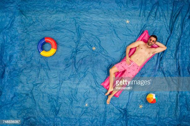 Man with sunglasses relaxing on his airbed