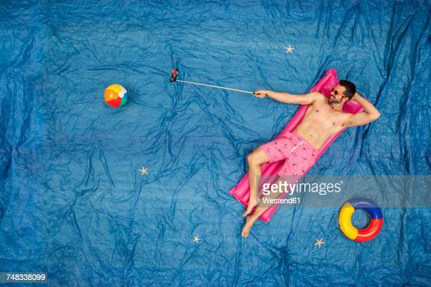 Man with sunglasses relaxing on his airbed, taking a selfie