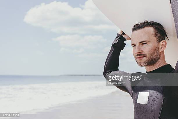 Man with surfboard at beach.