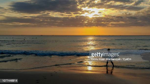 Man With Surfboard Walking On Beach Against Sky During Sunset
