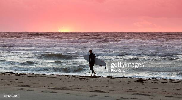 Man with Surfboard walking on beach at sunset