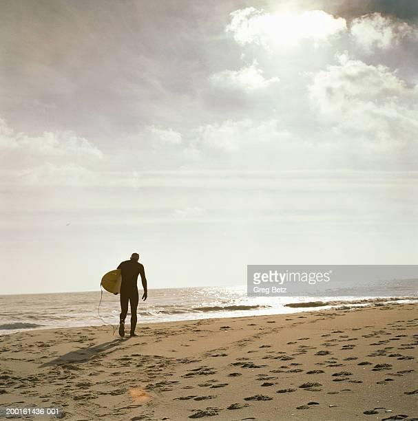 Man with surfboard walking toward ocean, rear view