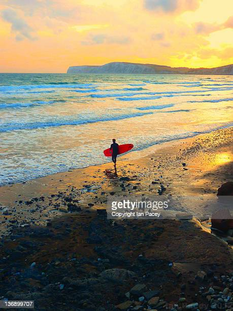 man with surfing board at beach - compton bay isle of wight stock pictures, royalty-free photos & images