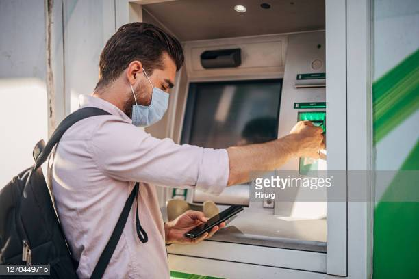 man with surgical mask using atm machine - ginger banks stock pictures, royalty-free photos & images