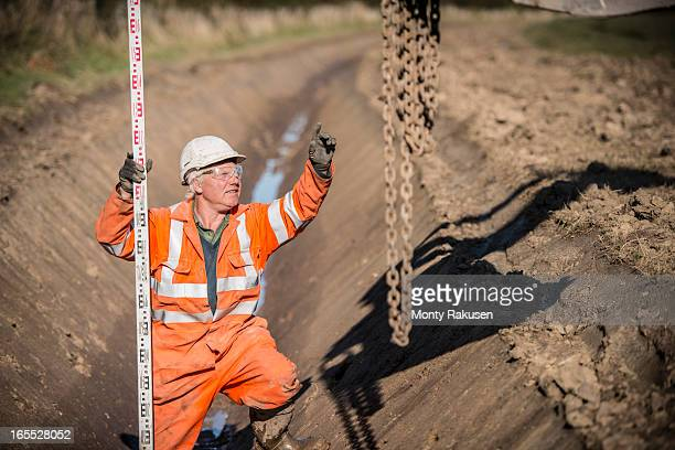 Man with surveyors measuring stick digging drainage channel at surface coal mine restoration