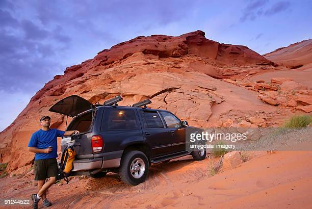 man with SUV and sandstone desert landscape