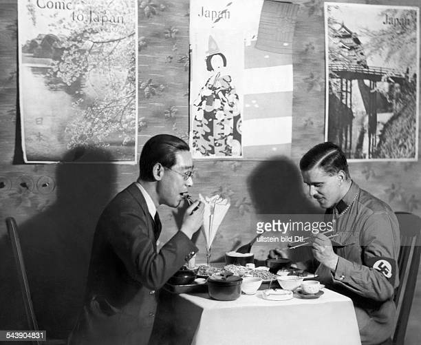 Man with swastika armband and japanese man eating Japanese food Photographer Curt Ullmann Published by 'Sieben Tage' 12/1934Vintage property of...
