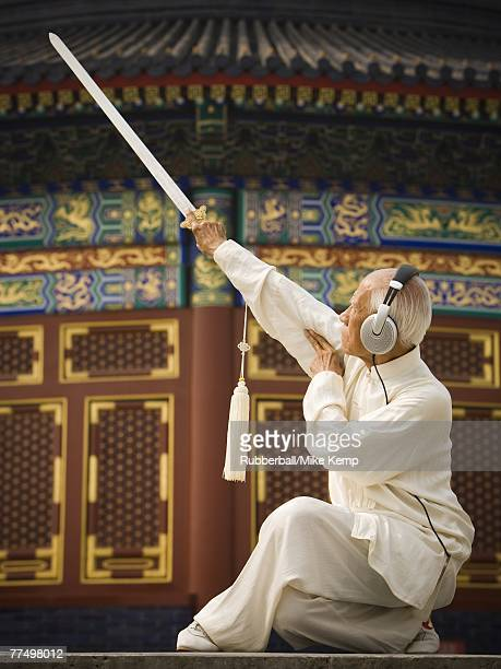 Man with sword doing Kung Fu with headphones