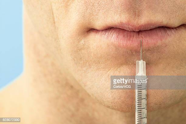 Man with Syringe at Lips