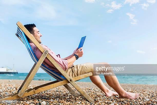 man with tablet at beach. - transat photos et images de collection