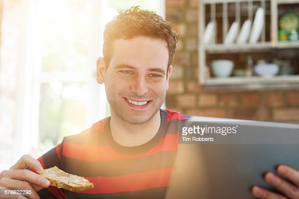 man with tablet eating toast - messa a fuoco differenziale foto e immagini stock