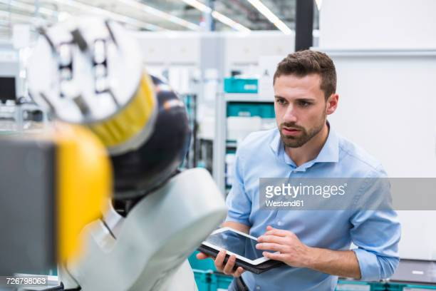 man with tablet examining assembly robot in factory shop floor - industriebetrieb stock-fotos und bilder