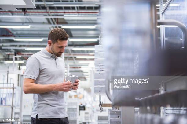 Man with tablet in factory shop floor examining products