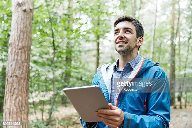 man with tablet in forest - botanist stock pictures, royalty-free photos & images