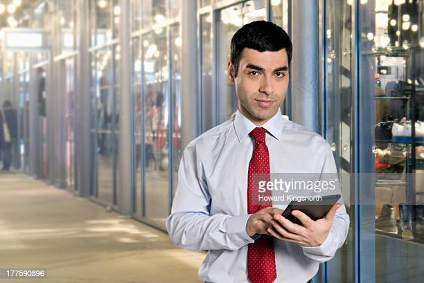 man with tablet in shopping centre