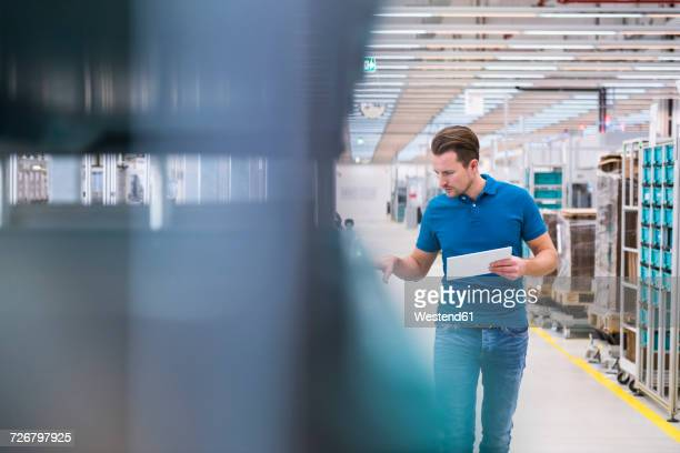 man with tablet looking at tugger train in industrial hall - lagerhalle stock-fotos und bilder