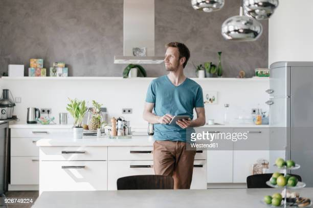 man with tablet standing in the kitchen looking at distance - mid adult men stock pictures, royalty-free photos & images