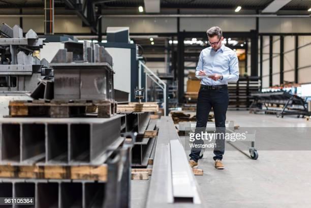 man with tablet standing on factory shop floor - halle gebäude stock-fotos und bilder
