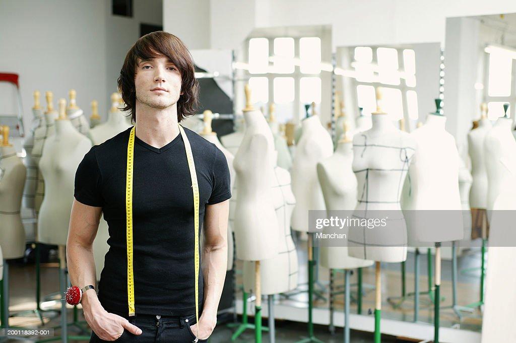 Man with tape measure round neck in fashion studio, portrait : Stock Photo