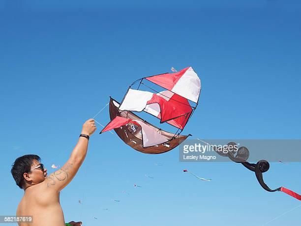 Man with tattoo flies pirate ship kite