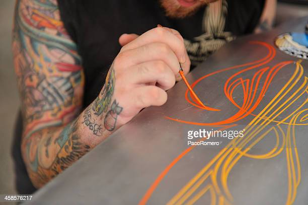 man with tattoo painting stripes on restored old american car - hot rod car stock photos and pictures