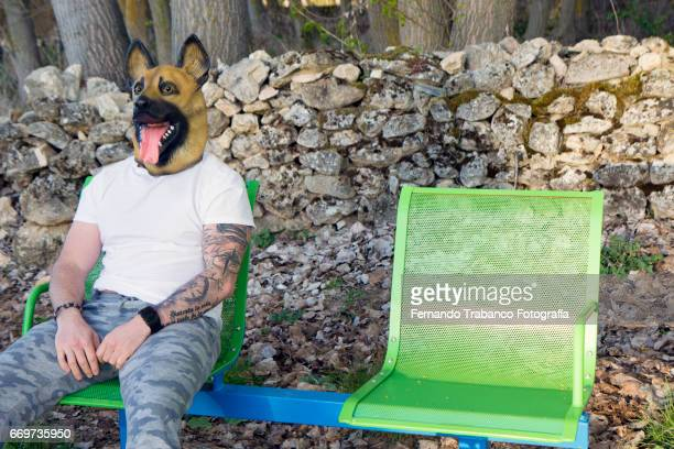 Man with tattooed arm and German Shepherd dog mask sitting on a bench in a park