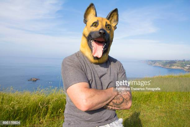 Man with tattooed arm and German Shepherd dog mask with arms crossed by the sea