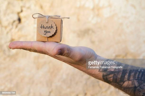 Man with tattooed arm holds in his hand a small cardboard box with a thank you gift