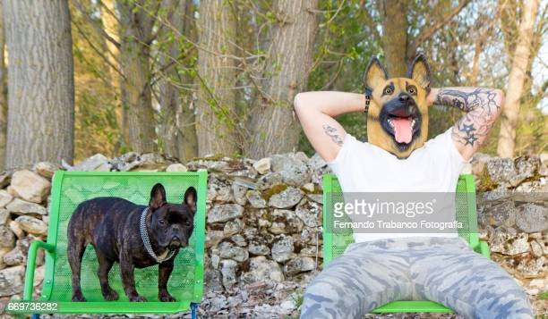 man with tattooed arms on head sitting with his dog next to him disguised with dog mask - dog mask stock pictures, royalty-free photos & images